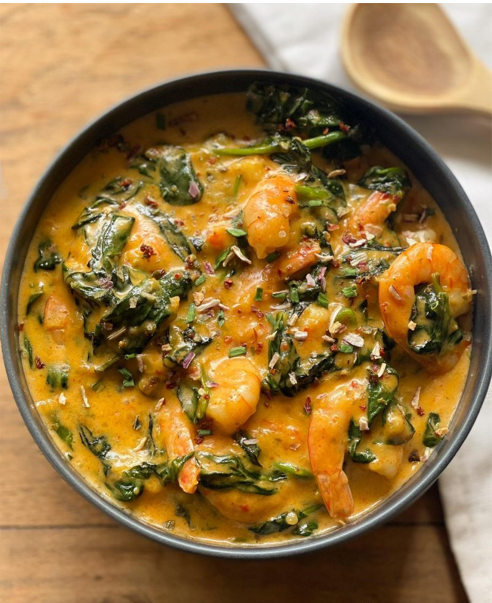 Exotic and healthy recipe for shrimps with red curry and fresh spinach